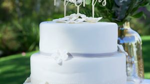 Simple White Wedding Cake with birthday tag placed on table 4K 4k