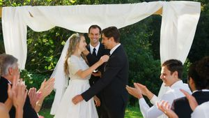 Happy groom showing off wedding ring and happily kissing, hugging bride 4K 4k