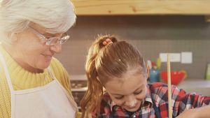 Little girl mixing the batter and happy grandmom guiding her 4K 4k