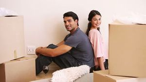 Couple sitting back-to-back in a room with boxes