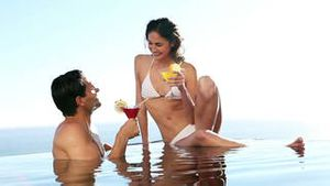 Couple in a swimming pool drinking cocktails