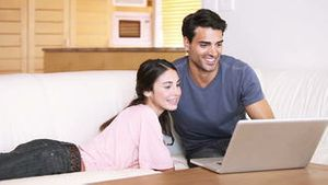 Smiling couple looking at a laptop