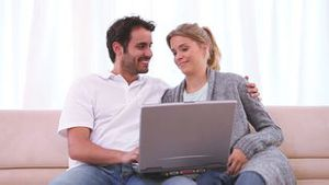 Couple sitting together on the couch while looking at a laptop