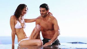 Smiling couple sitting in a swimming pool