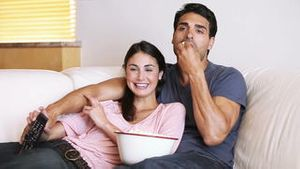 Laughing couple watching the television