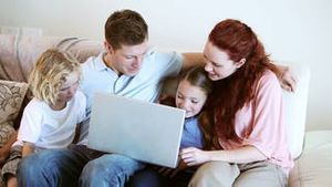 Smiling family looking at a laptop