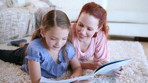 Cute child reading a book aloud with her mother
