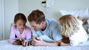 Father reading a book with his children