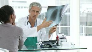 Mature doctor and his patient examining an xray