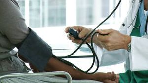 A doctor checking a patients blood pressure