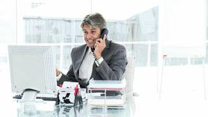 Lucky businessman on phone celebrating a success