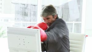 Stressed businessman wearing boxing gloves