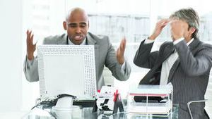 Two disappointed businessmen working at a computer