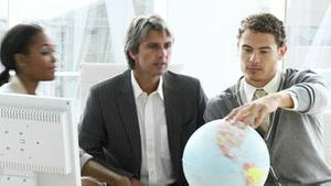 United business people looking at a terrestrial globe