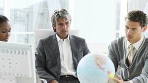 Ambitious business team looking at a terrestrial globe