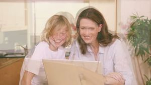 Mother and son with a laptop in the kitchen