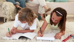 Siblings doing their homework on the living room floor with their parents behind them
