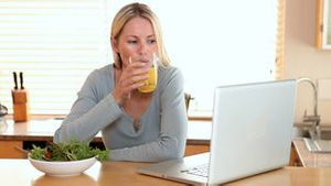 Woman with a laptop takes a drink of orange juice