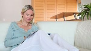 Woman reading a magazine before looking ahead of her
