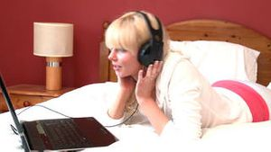 Attractive woman lying down on bed listening music