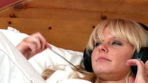 Pensive woman lying on bed listening music