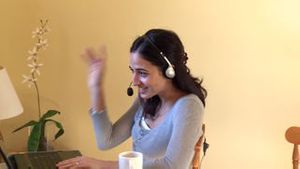 Jolly woman talking on internet with headset on