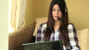 Happy woman working at a laptop with headset