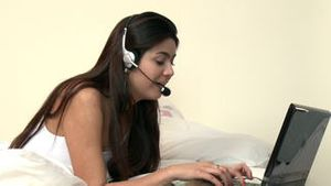 Animated woman lying down on bed using a headset