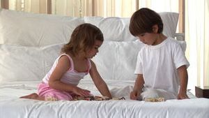 Wellbehaved children playing on the bed