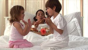 Attentive parents eating breakfast and children playing