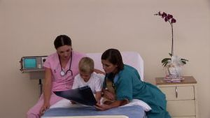 Two positive nurses showing Xray to a little boy