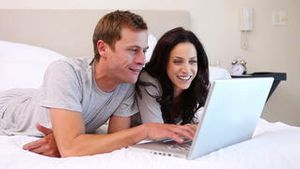 Couple using laptop on their bed