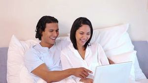 Couple sitting on the bed with laptop