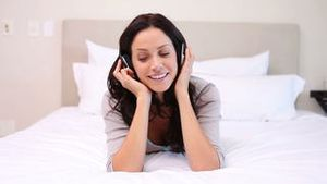 Woman on her bed moves to the music she is listening to