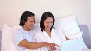 Couple in a bed using a laptop