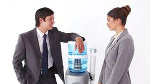 Business people talking next to the water cooler