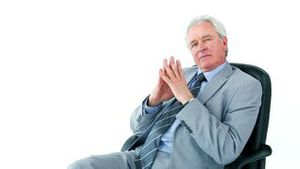 Serious businessman sitting on a swivel chair