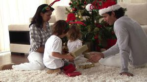 Happy family discovering the gifts on Christmas day