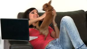 Pretty woman and her dog using a laptop