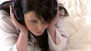 Young woman listening music lying down on bed