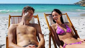 Smiling couple lying on deck chairs