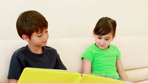 Happy siblings reading a book