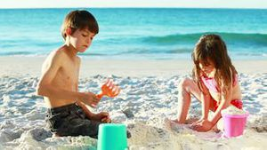 Siblings building sand castles
