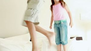 Happy siblings jumping on a mattress