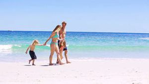 Smiling family walking on the sand