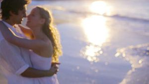 Side view of couple kissing on the beach during sunset