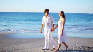 Couple holding hands while walking along the beach