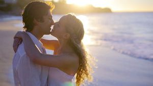 Couple kissing on the beach during the sunset