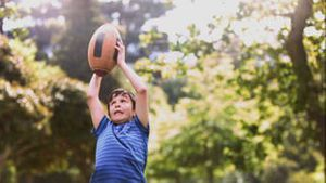 Child playing in slow motion with a rugby ball