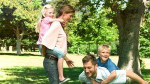 Parents in slow motion giving their children a piggyback